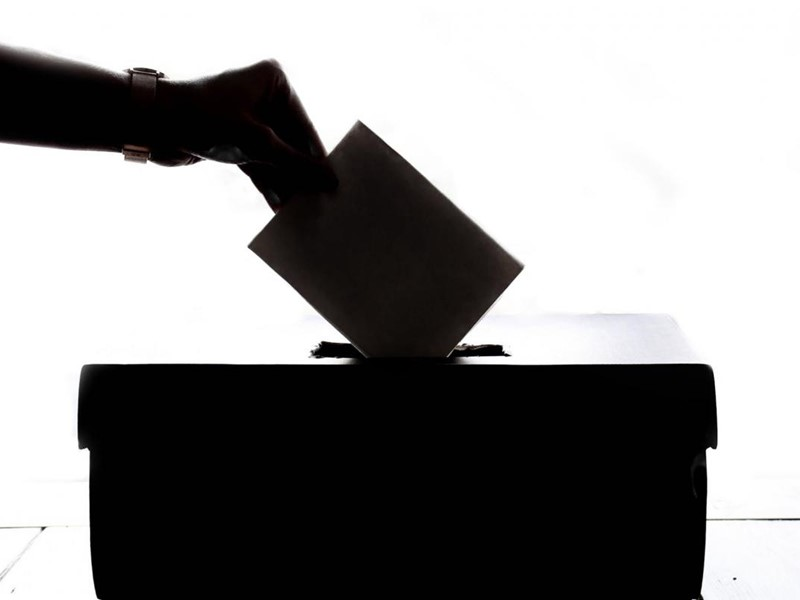 A hand putting a voting ballot into a ballot box