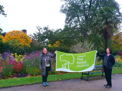 Cllr Mary Lea and Jill Thompson holding the green flag in the Sheffield Botanical Gardens with colourful plants in the background