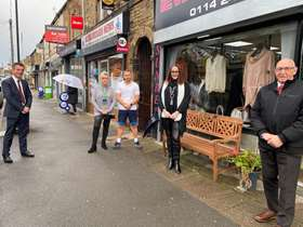 Four people stood distanced outside shop front on high street