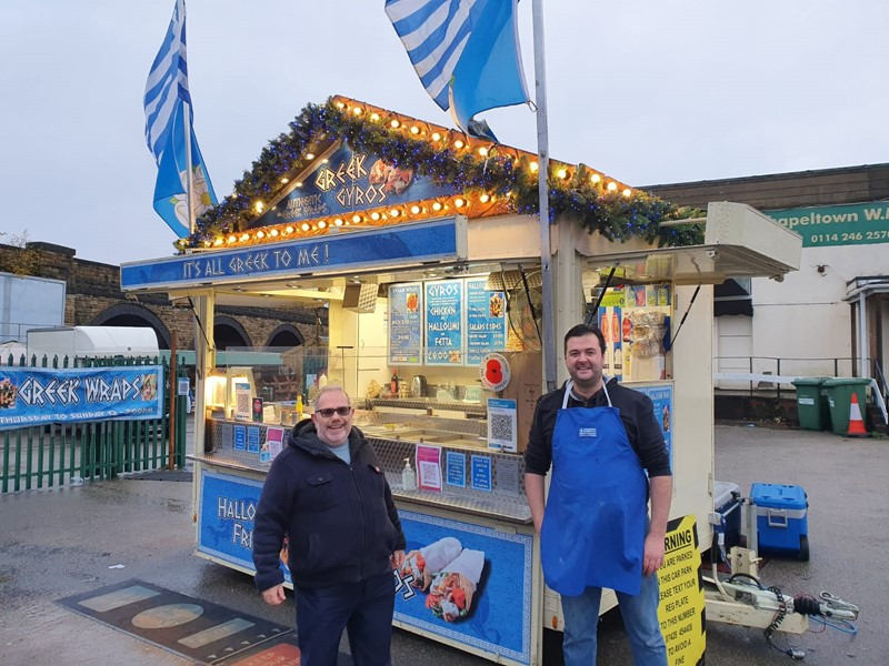Two men stood in front a Greek food stand, one in an apron.