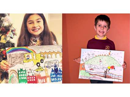 Two children hold up gritter designs on paper