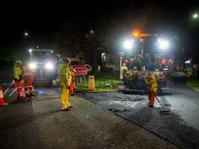 Roadworkers laying tarmac in the dark