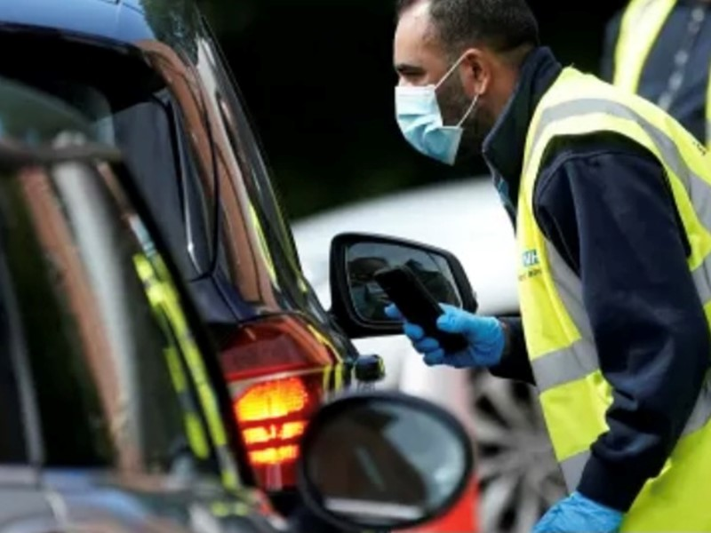 Man with mask in hi-vis as driver door of car at testing centre
