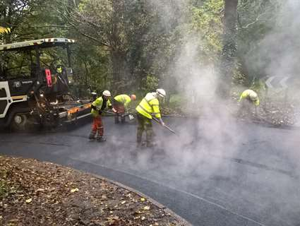 Workers tarmac road surrounded by trees