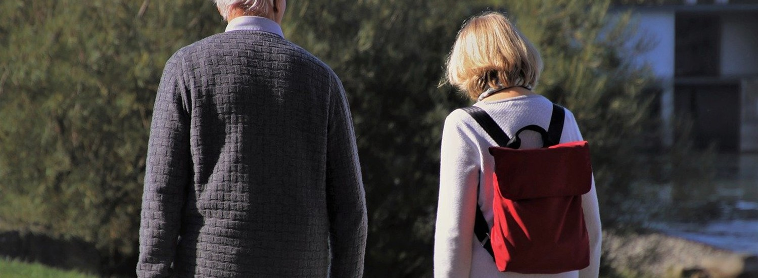 Older man walking with woman outdoors