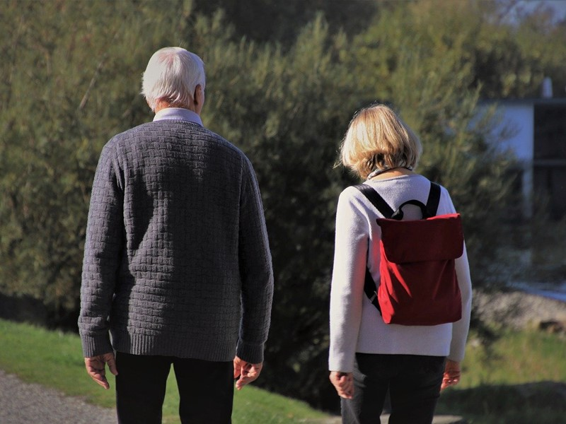 older man walking outdoors with woman