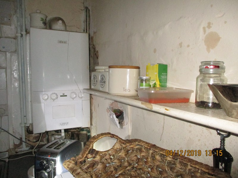 Part of a kitchen in disrepair with damaged walls