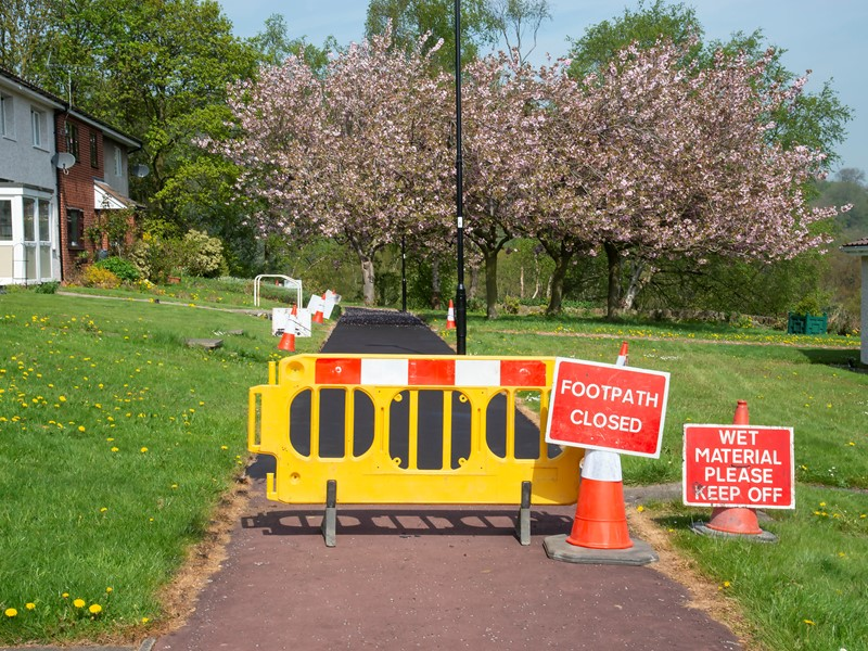 Barriers and signs in front of resurfaced pavement
