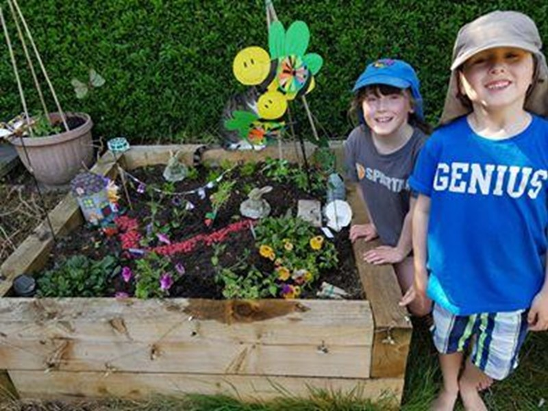 Two boys stand next to a fairy garden they have made
