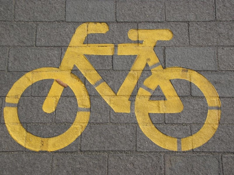 Yellow cycle path sign on a path