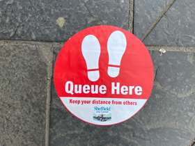 A sticker on the floor to mark social distancing measures