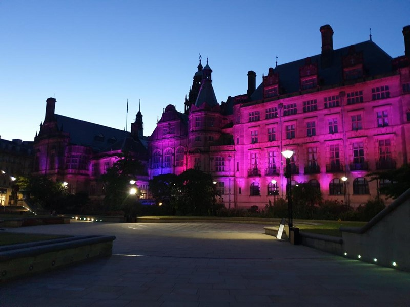 Sheffield town hall lit up at dusk with purple lights