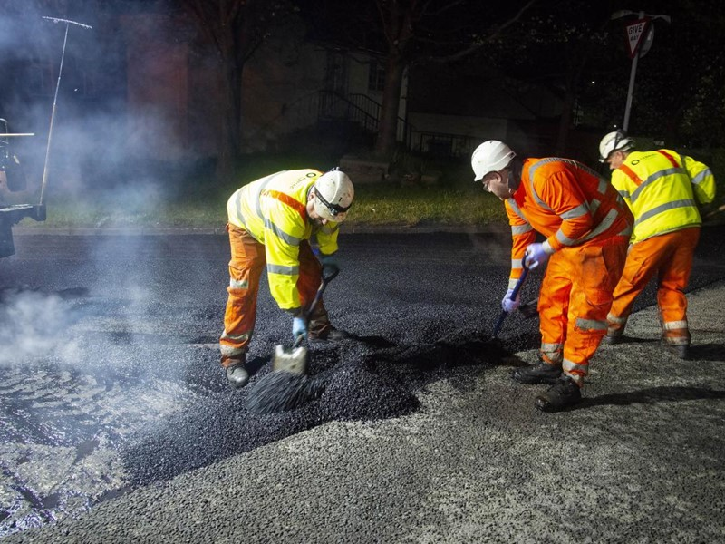A photograph of workmen shovelling tarmac on to a road
