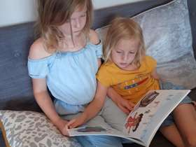 Photograph of two children reading a book