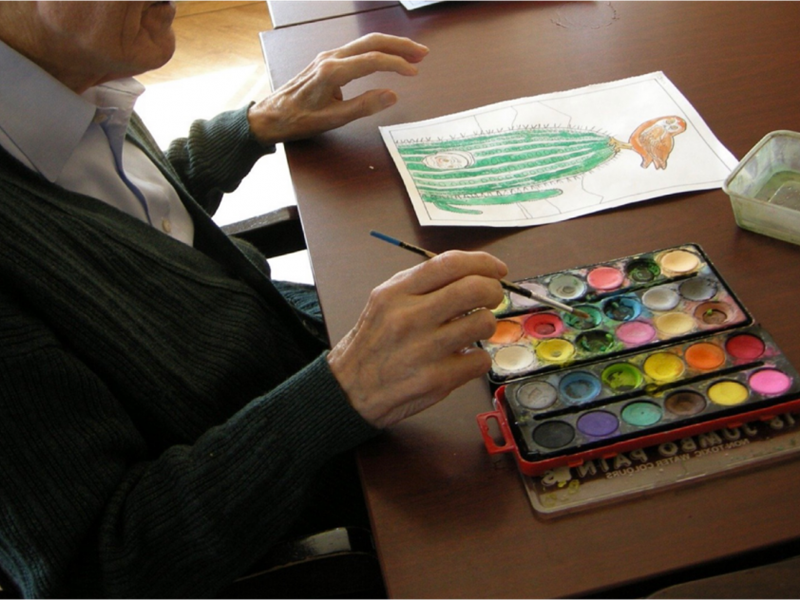 Older person doing crafts at a table