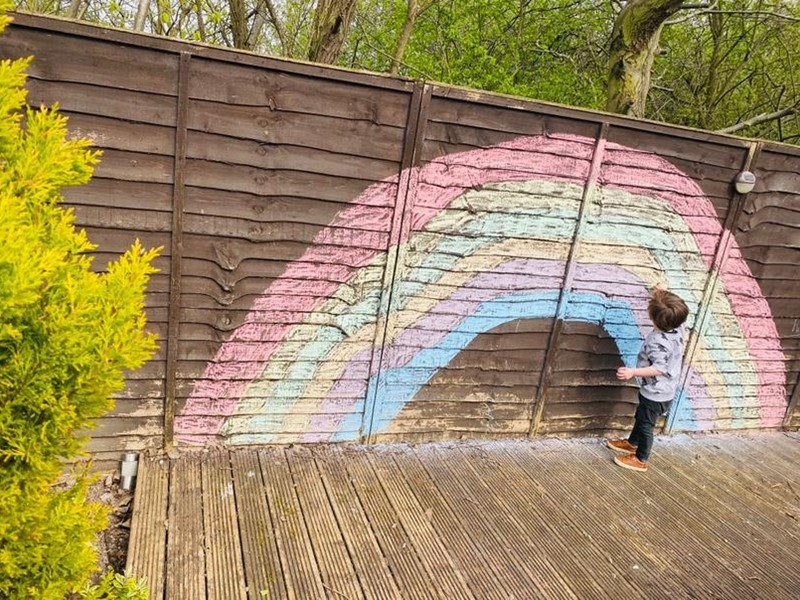 Chalk rainbow drawn on a fence