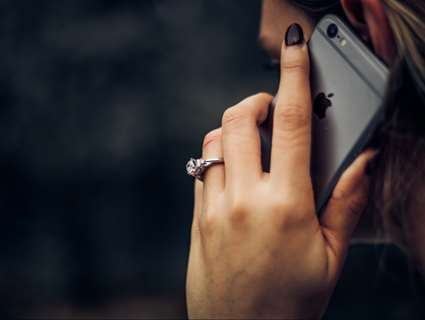 close up of hand holding a phone to an ear