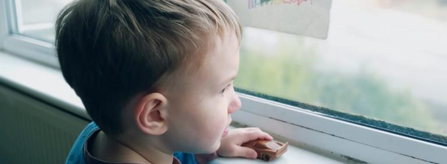 Young boy looks out of a window decorated with a rainbow