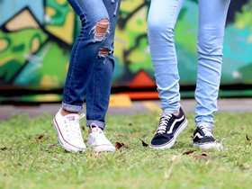 two pairs of teenage legs in jeans and trainers