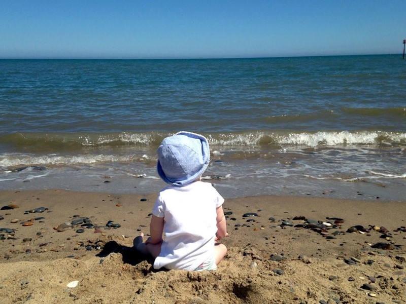 young child sat on the beach