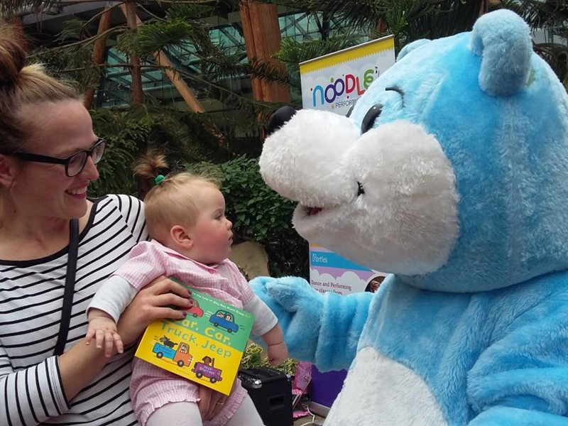 Blue bear mascot with a baby and mum